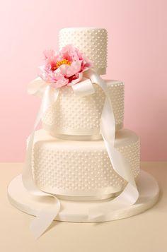 Three tier fondant wedding cake with royal icing dots, satin ribbon and sugar peony.