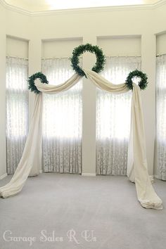 Pretty for a winter wedding arch. Backdrop of curtains curtains at windows add 3 wreaths add long fabric so drapes on floor and frames space