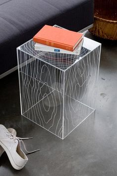 This accent table playfully fuses woodgrain patterns onto a five-sided acrylic box, juxtaposing organic lines with modern materials. It can be flipped over to create an elegant storage solution. Looks