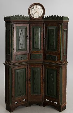 "FOLK ART CLOCK CABINET, Swedish, marked ""Erik Åkers"" and dated 1878. Pediment with integral clock and leaf ornament. Weights and pendulum in mid section. Two cabinets with shelving interior. Rhombus decoration on the front. Length ca 130 cm, depth ca 88 cm, height 208 cm. Key included."