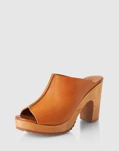 Die Pantoletten von Apple of Eden überzeugen durch die Holzsohle mit Plateau und dem schönen braunen Obermaterial. Perfekt zum Kleid oder Rock.