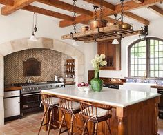 In this kitchen, detail reigns supreme from the herringbone tilework in the range niche to the antique ladder-turned-pot rack to the rough-hewn beams on the ceiling. Shades of copper and brown create a warm welcome in the texture- and character-rich space.
