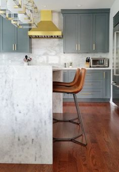 waterfall countertops, brown leather chairs with the gray cabinets & gold fixtures