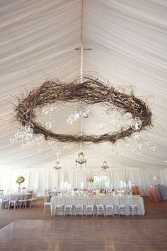 Un centro de mesa colgante suspendido sobre todas las mesas. Mezcla de ramas y luces uniendo así la boda rústica y la industrial, esta decoración de boda es increíble. Fotografia Sarah Kate y diseño floral de jacksondurham