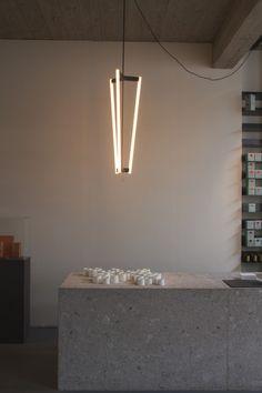 Magazyn Shop in Antwerp, Belgium,   The Tube Chandelier by London-based Greek lighting designer Michael Antassiades hangs above the island.