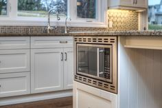 Custom cabinetry with built-in microwave. Kitchen Cabinetry, Kitchen Flooring, Toilet Tiles, Open Concept Great Room, Classic White Kitchen, Double Closet, Double French Doors, Built In Microwave, Floor Drains