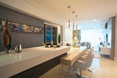 Logo na entrada do apartamento, os arquitetos projetaram um móvel de bar, formado por uma mesa em silestone, com poltronas giratórias em couro branco, e balcão alto com tampo em marmoglass branco e cooler incorporado no próprio móvel.
