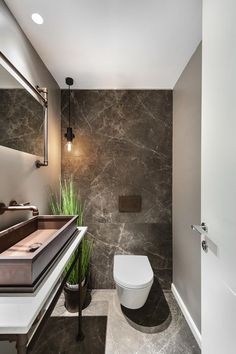a chic guest toilet with stone tiles, a large metal sink, a fake potted plant an. a chic guest toilet with stone tiles, a large metal.