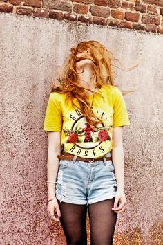 Yellow guns n roses shirt. Tucked in denim shorts. Black fishnets. Red headed girl.