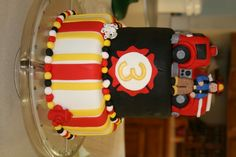 Fire Truck Birthday Cake - 2-tiered, fondant covered birthday cake with fondant fireman, dalmatian, and hydrant.  Fire truck is made from cake carved into truck shape covered in fondant.