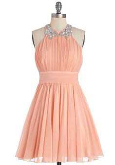 Any set of arms you spin into while wearing this peach party dress will be pleased to dance in style! The hook-and-eye halter of this dress is lovely-fied by iridescent beads and an intricately pleated bodice that looks sweet while you samba. As you kick and spin in strappy silver heels and rhinestone jewelry, this lined, padded, and back-zipped dress dazzles onlookers with every peek of the tulle-tiered skirt lining they catch!