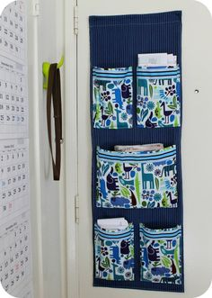 DiY Project: Sew a Fabric Mail Organizer for the Wall | theleftcoastmama - cute fabric for a kid's room - bed pocket organizer.  I like the pleats in the pockets on this one.