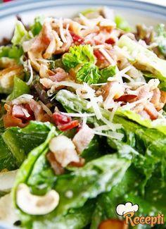 Recept za Cezar salatu. Za pripremanje salate neophodno je pripremi dimljenu slaninu, pileće bilo, parmezan, beli luk, tost hleba, zelenu salatu, paradajz, limun, pavlaku, majonez, maslinovo ulje, biber i so.