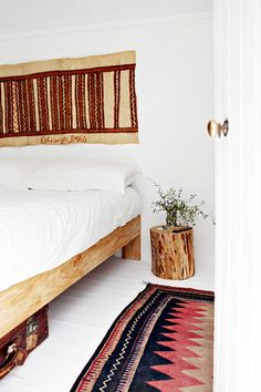 the rug is a vintage Afghan carpet, the artwork above the bed is an old bark tapa cloth from Papua New Guinea