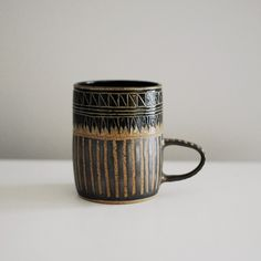 Hand-built in Brooklyn by Little Bear Pots, this handsome mug plus strong coffee equals a great start to any morning! Each mug is unique with hand-carved bands of geometric designs and unglazed stripe
