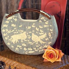 With the look of a treasure found on an exotic journey, our Adelita Handbag readies any outfit for adventure. Inspired by traditional Mexican textiles, this gorgeous artisan handbag is hand crafted from grey toned woven raffia and features intricate embroidered detailing of tropical birds and flowers, rich carved wood handles, cotton lining, and an interior slip pocket. #mothersday #gift #ideas #oliveandcocoa