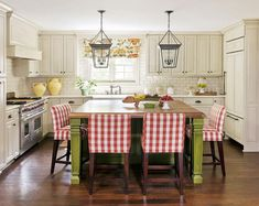 A pair of Small Cornice Hanging Lanterns illuminate a green kitchen island topped with butcher block lined with red plaid counter stools.