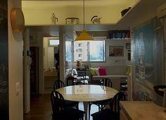 Sala de estar, sala de jantar e cozinha integrada. Piso de madeira, prateleiras, decoração colorida, organização de livros.