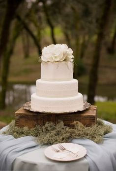 White wedding cake displayed on rustic  wooden  box