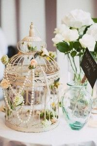 vintage birdcage with flowers and pearl wedding centerpieces
