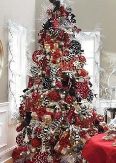 thinking black and white Damask Ribbon this year with red accents? I like the small wrapped packages on this tree as ornaments too.