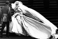 Lady Diana Spencer, soon to become the Princess of Wales, shows off her wedding gown for the first time as her bridesmaids set her train on arrival at Saint Paul's Cathedral on July 29, 1981.