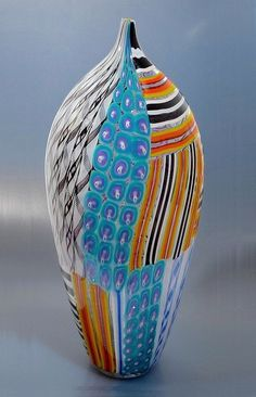 This elegant elongated balaster shaped necked vase was made in 2009 by Mike Hunter for Twists Glass. It comprises zanfirico, murrine and tessera canes in white, black, blue, purple, turquoise, red, orange and yellow, all laid out in a patchwork pattern. It is signed
