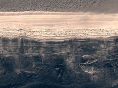 A piece of Mars: This is the edge of the northern polar cap on Mars. At the top is the icy surface, abruptly cut by a cliff. The cliff wall shows many layers of different materials -- the darker ones are old dunes. How cool is it to know that the polar ice cap on another planet is sitting on what used to be an enormous sand sea? It's like looking at limestone and shale on mountains here on Earth an imagining them once being at the bottom of an ocean. It blows my mind. (HiRISE…