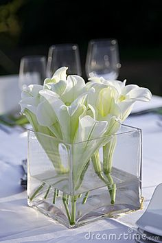 Table decorated for the wedding party on the table a vase of white lilies. Outdoor.