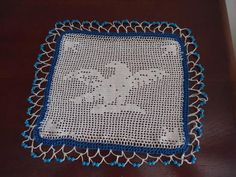 "From ebay: ""old crochet milk jug cover, measuring 22cm by 20cm. Filet crochet eagle design in the centre and blue glass bead weights."""