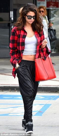 Selena Gomez donned a pair of leather-look sweats with high top black sneakers and added a tank with a red flannelette shirt