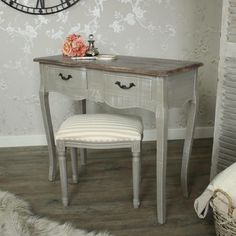 desk unevenly colored in grey, with matching stool, covered in cream and beige striped fabric, country chic décor, a small bouquet of roses, magnifying glas and perfume bottle