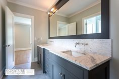 Beautiful bathroom boasts a charcoal gray shaker sink vanity featuring a pair of rectangular porcelain sinks framed by gray and white marble counters and matching backsplash which highlights modern wall mount faucets underneath a charcoal gray mirror illuminated by tubular vanity lights.