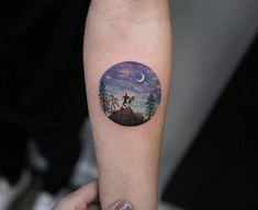 Night landscape circle tattoo on the left inner forearm.