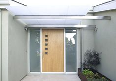 This contemporary front door design features five square windows in vertical row with a smooth, wooden base. Modern Entry Door, Modern Exterior Doors, Contemporary Front Doors, Wood Exterior Door, Door Entry, Modern Contemporary, Modern Design, Custom Design, Mid Century Modern Door