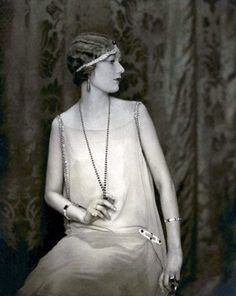 """Τα flapper dresses παίρνουν ζωή. Αναγνωρίσιμο της εποχής αποτελεί η κόμμωση """"αλά γκαρσόν"""", καθώς επίσης και τα μακρία κολιέ από μαργαριτάρια."""