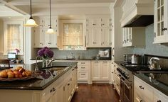 Kitchen, white cabinets, dark / black counters, light blue walls, wood floors. by Clou