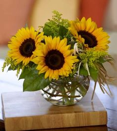 Pretty and simple arrangement: sunflowers, solidaster and lemon leaves in glass bubble bowl.