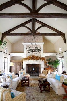 sofa placement by fireplace, wood beams, chandelier hanging from wood beams Fusch Architects, Inc.