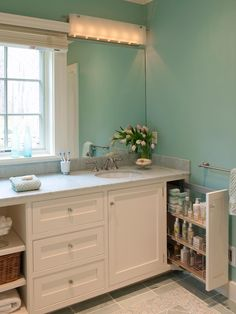 """""""Innovative storage solutions were key to making the most of every room in this waterfront cottage,"""" says designer Elizabeth Swartz. """"This included the use of some wonderful hardware, such as this Hafele pull-out unit in the master bath to organize even the smallest of spaces efficiently."""""""