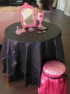 Create this simple glamour experience by draping black and pink cloth over a table and seat to make a Barbie touch up station. Here the girls can have fun playing with make up and hair accessories.