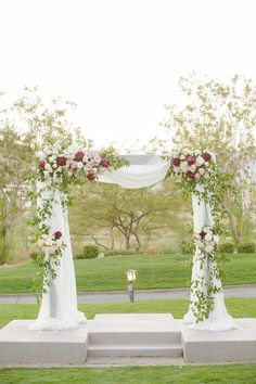 Wooden canopy/chuppah covered in draping with greenery and floral. Marsala and blush floral. Overlooking 18th hole of private golf course and Red Mountains. Las Vegas, NV