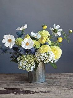Yellow and white summer time arrangement, set off by the interesting tin. Start with the hydrangeas, add thistles and dahlias and top with the cosmos.