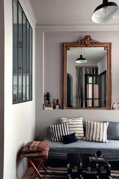 le coin salon avec dans la niche, un miroir de famille, une banquette-lit recouverte de tissu tissé main, Tensira chez Home Autour du monde, coussin noir, Caravane: