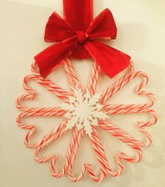 Easy DIY Christmas decor that you can purchase from the Dollar Tree! Candy cane wreath with a flat ornament using hot glue. So easy for DIY Christmas decor.