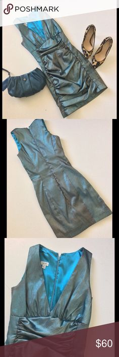 """Cache Cocktail Dress Short Prom Dress This stunning dress has a plunging v-neck & ruched skirt. Fitted. Back zip closure. The gorgeous fabric is turquoise with bronze metallic fabric that's shimmery. Fully lined. Excellent used condition. Worn once. Polyester, nylon & spandex w/ foil lining. Lining  is polyester & spandex. Dry clean. 30"""" bust 23"""" waist 28"""" hip length 30"""" from shoulder p. Shoes are sold. Wristlet listed separately in my closet #prom #homecoming #club Cache Dresses"""