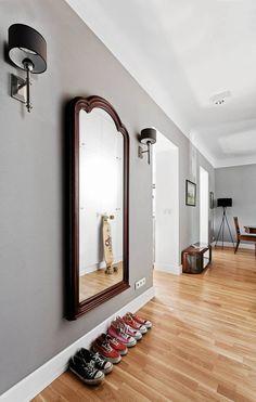 Przedpokój otwarto nakuchnię i połączono przejściami z salonem, dziękiczemu w dzień jestdobrze doświetlony naturalnym światłem. Ogromne lustro w ozdobnejramie kontrastuje zminimalistycznymi frontami szaf, którymi zabudowano całąścianę.