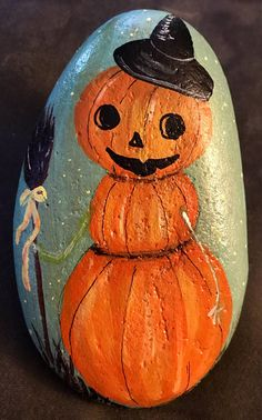 If you love snowmen, pumpkins and vintage, this amazing painted rock art is for you! I personally LOVE this one (and have one)! This whimsical vintage style pumpkin snowman is nicely detailed against a blue and shimmery green background. He is simply a must have unique addition to any Halloween decor.  This is painted to order so size and shape may vary slightly.  Painted rocks are fun, unique pieces of art that make wonderful display pieces, garden stones, paperweights, pet rocks, good luck…