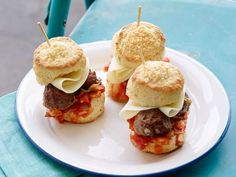 Meatball Sandwiches : Meatballs are a sure-fire game-day favorite. Alton Brown makes homemade Parmesan-parsley biscuits to craft a meatball sandwich that is topped with spaghetti sauce and provolone cheese.