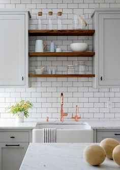 Light gray and white kitchen boasts a farmhouse sink paired with a copper gooseneck faucet fixed beneath stacked floating wooden shelves mounted on white subway backsplash tiles between gray shaker upper cabinets located above gray lower cabinets finished with oil rubbed bronze hardware and a marble countertop.